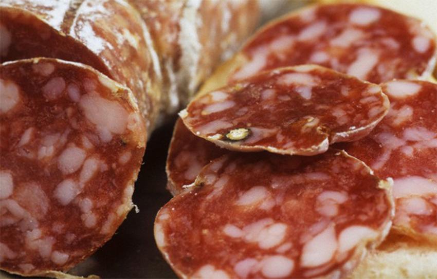 un parásito transmitido por alimentos que se encuentra en carne de cerdo cocida es